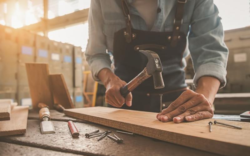 carpintero-que-trabaja-equipo-tabla-madera-tienda-carpinteria_1418-2326